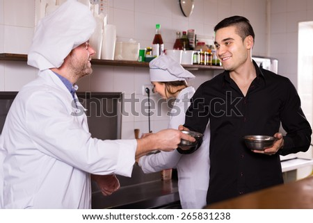 Portrait of happy young male waiter holding dishes and cooks at fastfood place