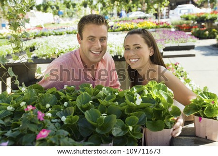 Portrait of happy young man and woman at botanical garden