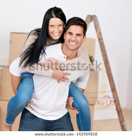 Portrait of happy young man giving piggyback ride to woman against cardboard boxes in new house - stock photo