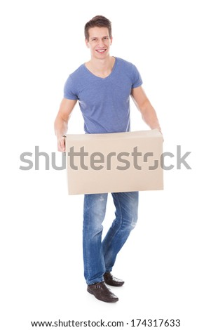 Portrait Of Happy Young Man Holding Cardboard Box Over White Background