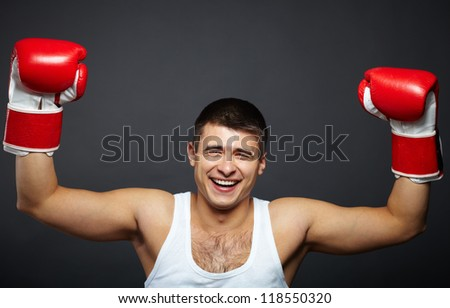 Portrait of happy young man in red boxing gloves looking at camera - stock photo