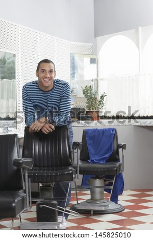 Portrait of happy young man leaning on chair in hair salon - stock photo