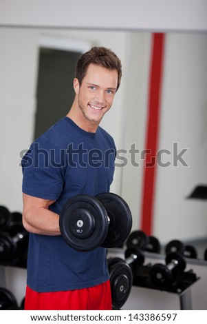 Portrait of happy young man lifting dumbbell in gym