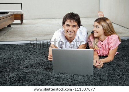 Portrait of happy young man lying on rug with laptop while woman looking at him