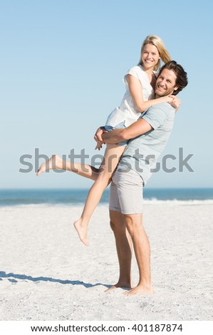 Portrait of happy young man picking up his girlfriend. Couple at beach enjoying on a sunny day. Happy young couple smiling at seaside. - stock photo