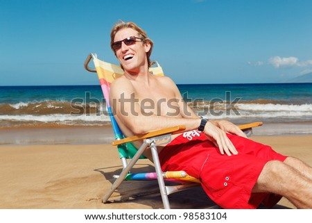Portrait of happy young man relaxing on the beach - stock photo