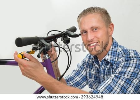 Portrait Of Happy Young Man Repairing Bicycle Handlebar - stock photo
