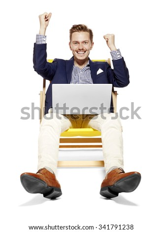 Portrait of happy young man sitting on sunbed. He raises his arms in a gesture of victory. - stock photo