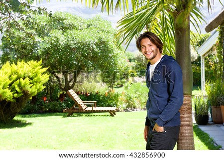 Portrait of happy young man standing against tree in backyard - stock photo