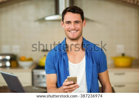 Portrait of happy young man using smartphone in kitchen