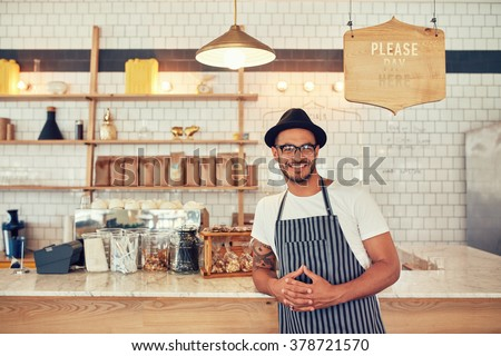 Portrait of happy young man wearing an apron and hat leaning to a cafe counter. Male barista standing at coffee shop looking at a camera and smiling. - stock photo