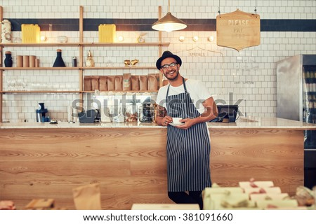 Portrait of happy young man wearing an apron and hat standing at a cafe counter holding a cup of coffee. Coffee shop owner looking at a camera and smiling. - stock photo