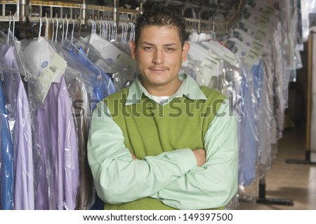 Portrait of happy young man with arms crossed standing in front of clothes rail