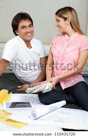 Portrait of happy young man with woman holding color swatches while sitting on rug with tablet PC and blueprints