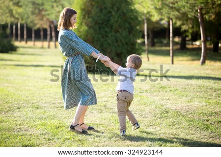 Portrait of happy young mom and her adorable little son playing and dancing together in park in summertime, smiling mother and kid holding hands, spinning, having fun together, full length - stock photo