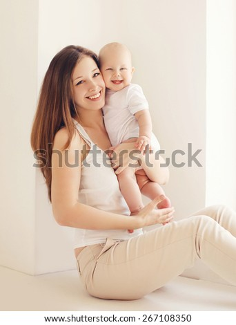 Portrait of happy young mother and baby having fun together at home in white room near window - stock photo