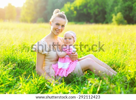 Portrait of happy young mother and baby little daughter wearing a dress together sitting on the grass meadow in sunny summer day, evening sunset sunlight