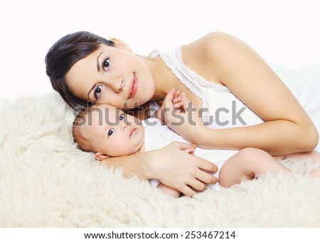 Portrait of happy young mother and baby lying on the bed at home - stock photo