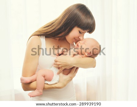 Portrait of happy young mother and baby on hands at home - stock photo