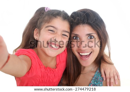 portrait of happy young mother and her daughter taking self portrait on a white background