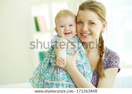 Portrait of happy young mother holding her little daughter - stock photo