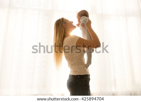 Portrait of happy young mother lifting up her baby against big window - stock photo