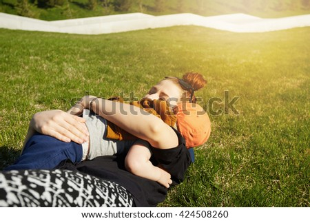 Portrait of happy young mother spending great time with her adorable two-year old son, hugging him in tenderness while lying on the grass in the public garden during walk in the morning. Flare sun - stock photo
