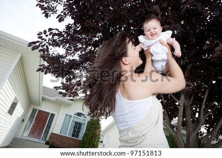 Portrait of happy young mother with baby girl outdoors