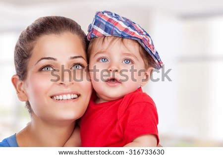 Portrait of happy young mother with cute little son at home, with pleasure spending time together, enjoying motherhood - stock photo