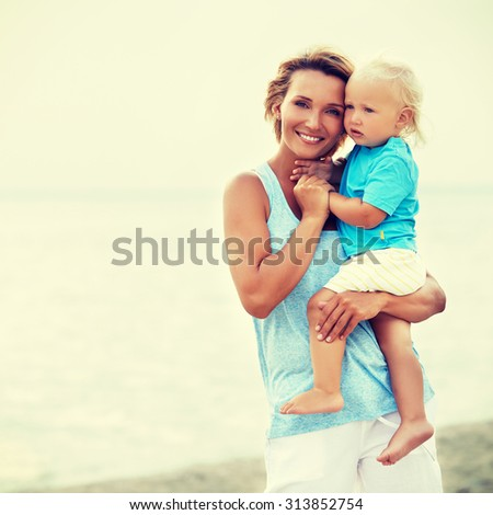 Portrait of happy young mother with little son standing on the beach. - stock photo