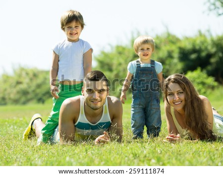 Portrait of happy young parents with children in grass at park