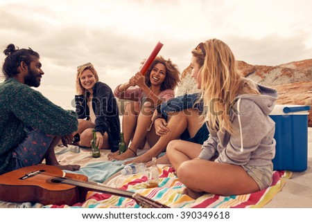 Portrait of happy young people having fun at beach party. Group of friends having a beach party together and celebrating with confetti. - stock photo