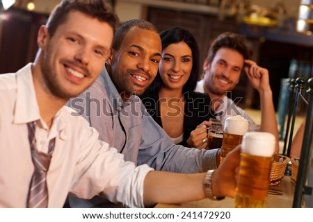 Portrait of happy young people sitting in pub, drinking beer, looking at camera, smiling. - stock photo