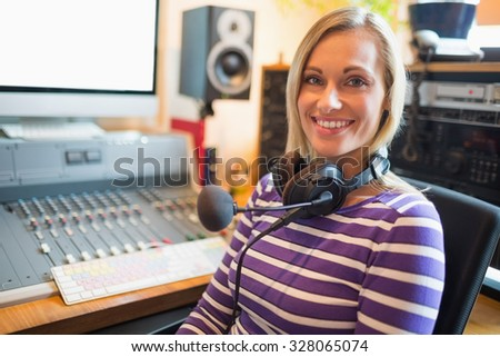 Portrait of happy young radio host sitting on chair in studio - stock photo