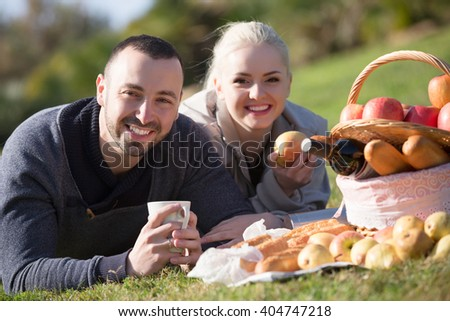 Portrait of happy young spouses lounging in sunny spring day at picnic outdoors - stock photo