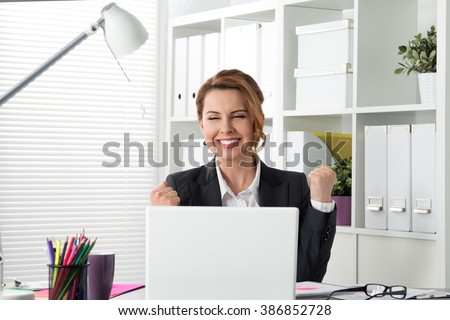 Portrait of happy young successful businesswoman celebrate something with arms up. Happy woman sit at office and look at laptop. Positive emotion. Big deal, promotion, lottery win or discount concept - stock photo