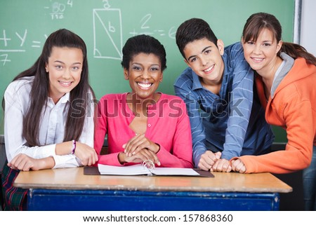 Portrait of happy young teacher with teenage students at desk in classroom - stock photo