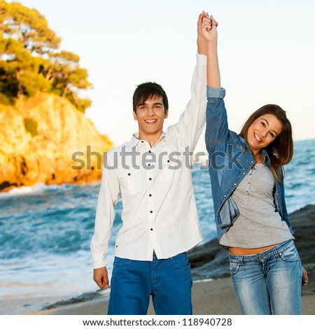 Portrait of happy young teen couple raising arms at seaside. - stock photo