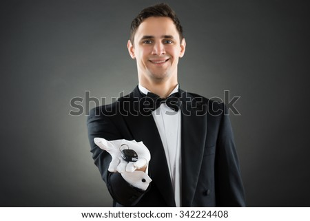 Portrait of happy young waiter giving car keys against gray background - stock photo