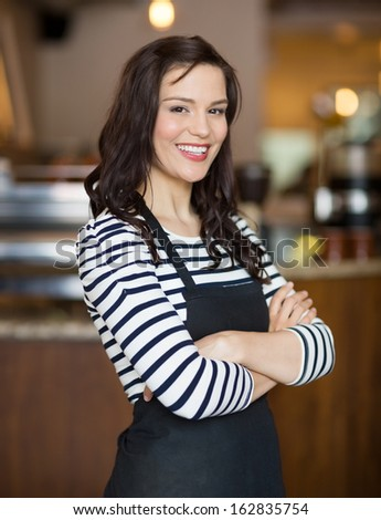 Portrait of happy young waitress standing arms crossed in cafe - stock photo