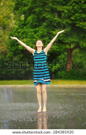 Portrait of happy young white Caucasian girl in blue dress jumping in puddles during rain thunderstorm on bright summer day outside, recreation leisure activity freedom concept, freeze motion effect - stock photo