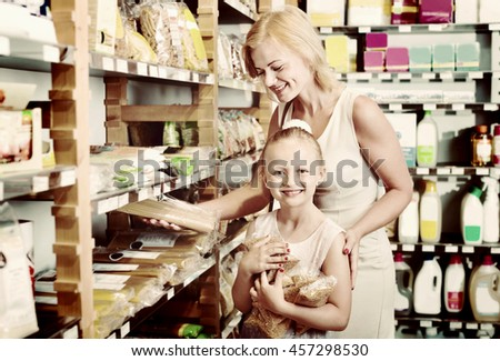Portrait of happy young woman and  cute cheerful girl gladly shopping different kinds of pasta in supermarket - stock photo