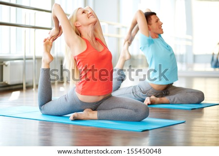 Portrait of happy young woman and man doing stretching exercise in gym