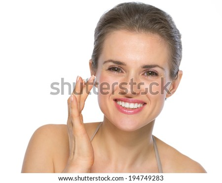 Portrait of happy young woman applying creme on face