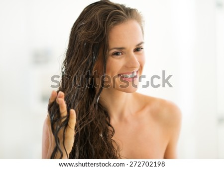 Portrait of happy young woman applying hair mask in bathroom - stock photo