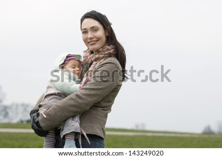 Portrait of happy young woman carrying sleeping baby in park - stock photo