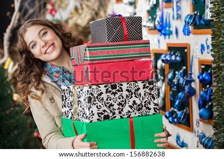 Portrait of happy young woman carrying stacked gift boxes in Christmas store - stock photo