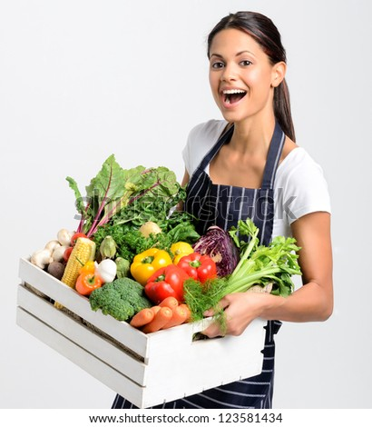 Portrait of happy young woman chef holding a crate full of fresh organic vegetables on grey background, promoting eating seasonally and sourcing from local producers - stock photo