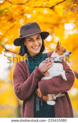 Portrait of happy young woman dog outdoors in autumn - stock photo