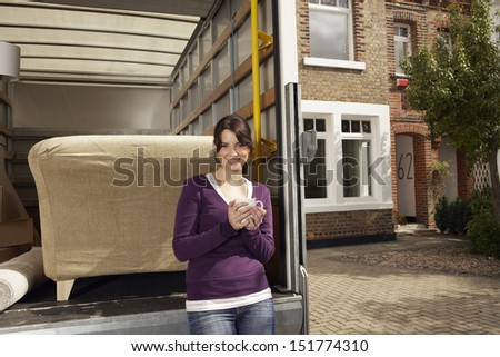 Portrait of happy young woman having coffee by moving truck in front of new home - stock photo